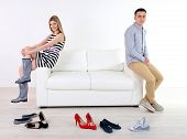 Loving couple choose new shoes, on light background