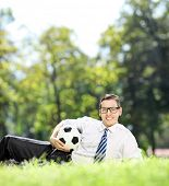 Young man lying on grass and holding a football in park shot with tilt and shift lens