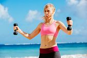 Fitness woman with barbells working out. Exercising outdoors at the beach.