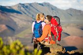 Two hikers relaxing and kissing, enjoying the amazing view from the mountain top.
