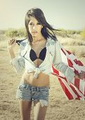 Beautiful young woman wearing denim shorts and top holding American flag in desert location
