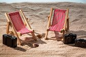 kkleine deck chairs on the sandy beach with suitcase