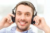 technology, music and happiness concept - smiling young man in headphones at home