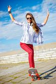 summer holidays, leisure and teenage concept - smiling teenage girl in sunglasses riding skate outsi