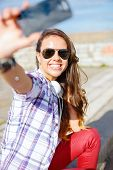 holidays and tourism concept - smiling teenage girl taking picture with smartphone camera aoutdoors