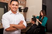stock photo of barber  - Handsome young barber shop owner smiling and managing his business