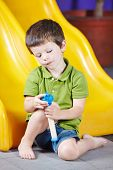 Boy playing alone with a toy in a kindergarten
