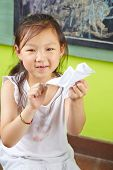 Asian girl doing origami bird of paper in a kindergarten