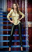 stock photo of black pants  - Attractive brunette woman with long hair in elegant yellow blouse and black leather pants standing in front of a stair in a nightclub - JPG
