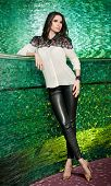 Attractive brunette woman with long hair in elegant black and white blouse and black leather pants