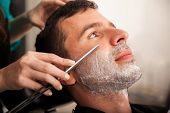 stock photo of barber razor  - Portrait of a young man getting his beard shaved by a lady barber - JPG