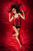 stock photo of bustiers  - Sexy young woman in lingerie and mask on red velvet background - JPG
