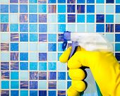 Hand in yellow protective glove holding spray bottle cleaning mosaic wall
