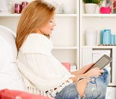 Woman using electronic tab sitting in couch