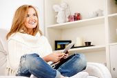 Happy woman relaxing at home with digital tablet