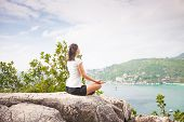 picture of samadhi  - Yoga meditation in lotus pose by woman on the peak of mountain - JPG