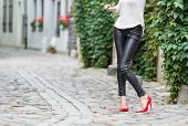 image of black pants  - Woman wearing black leather pants and red high heel shoes in old town - JPG