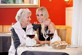 image of niece  - Old and Young Blond Women at Table Having Snacks at the Restaurant with Wine Water and Bread on the Table - JPG