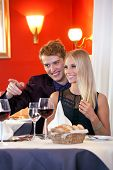 Smiling Couple Looking At Other Side In Restaurant