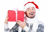 pic of crazy hat  - Happy smiling young man in Santa Claus hat with gift box isolated on white background - JPG
