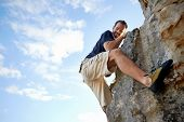 Man finding a foothold while climbing down a steep piece of mountain with copyspace