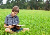 Boy sitting in grass reading a book in a summer field