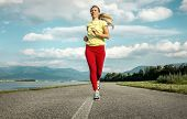 Beautiful female running on road under sky with sun light