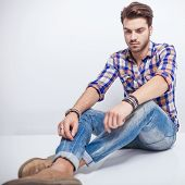 Side view of a handsome young man looking down while sitting on the floor with his legs crossed.