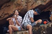 A couple taking a break in a cave from hiking