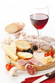 Wineglass With Red Wine And Assortment Of Snacks On White Background