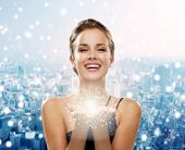 people, holidays, christmas and magic concept - laughing woman in evening dress holding something over snowy city background