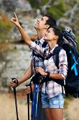 A hiking couple pointing upwards while looking up at the view