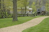 stock photo of split rail fence  - Gravel walkway running through a grass yard in the countryside. Wooden barns are visible behind a split-rail fence. Horizontal shot. ** Note: Slight blurriness, best at smaller sizes - JPG