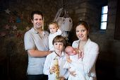 Happy Young Family With Three Children Celebrating The Baptism Of Their Newborn Baby Son