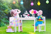 foto of little young child children girl toddler  - Two happy children cute curly toddler girl and a little baby boy brother and sister enjoying a tea party with their toys playing with dishes cup cakes and muffins in a sunny summer garden