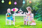 image of little young child children girl toddler  - Two happy children cute curly toddler girl and a little baby boy brother and sister enjoying a tea party with their toys playing with dishes cup cakes and muffins in a sunny summer garden