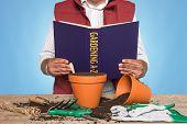 A gardener standing at a workbench reading a GARDENING A-Z book