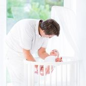 Young Smiling Father Putting His Newborn Baby In A White Round Crib Standing At A Big Window