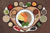 Large health food selection in bowls on a heart shaped wooden board over lokta paper background.
