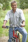 Senior Man Enjoying Cycle Ride In The Countryside