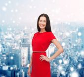 christmas, holidays, valentine's day, celebration and people concept - smiling woman in red dress over snowy city background