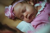 Image of cute little girl in pink suit indoor. Newborn baby