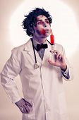 a scary zombie doctor with a syringe with blood, with a filter effect