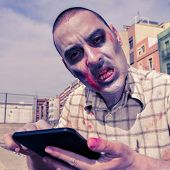 a scary zombie using a tablet computer, with a filter effect