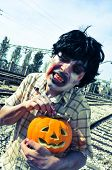a scary zombie with a carved pumpkin at abandoned railroad tracks, with a filter effect
