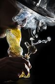 image of bong  - studio shoot with model simulating smoking pot through a bong in a dark high contrast image - JPG