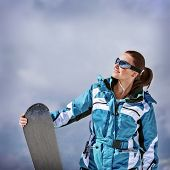 Cute young snowboarder girl having fun outdoors, cloudy sky, ski resort, spending winter vacation in the mountains