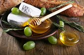 Camembert cheese on plate, honey, grapes, nuts and bread on wooden background