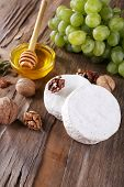 Camembert cheese, nuts, grapes and honey in glass bowl on wooden background