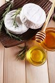 Camembert cheese on plate, honey in glass bowls on wooden background